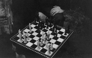 a picture of someone sitting at the corner while playing chess